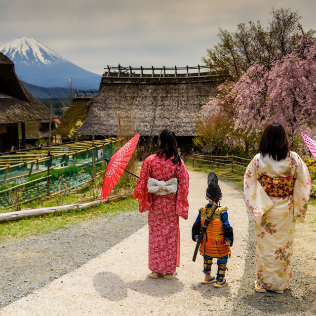 """Little samurai boy with sword and Two Kimono Japanese women at Saiko Iyashi no Sato Nenba, former farming, village near Mountain Fuji, Japan. Preserved wooden thatched roof houses near lake Saiko."" stock image"