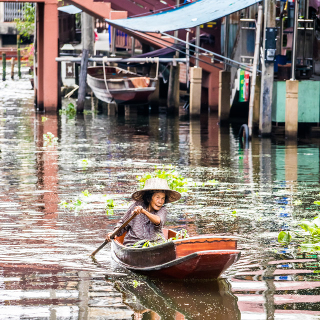 """A woman paddles her boat"" stock image"