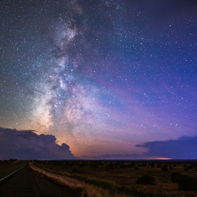 """The Milky Way and night sky with distant thunderstorms."" stock image"