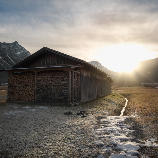 """Barn with firewood at sunset in the Alps"" stock image"