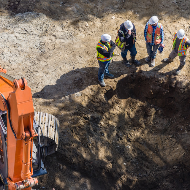 """Four men discussing a hole they just dug"" stock image"