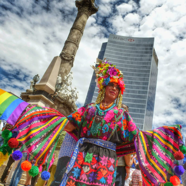 """A person in a colourful dress poses in front of the Angel de la Independencia, Mexico City, Mexico"" stock image"