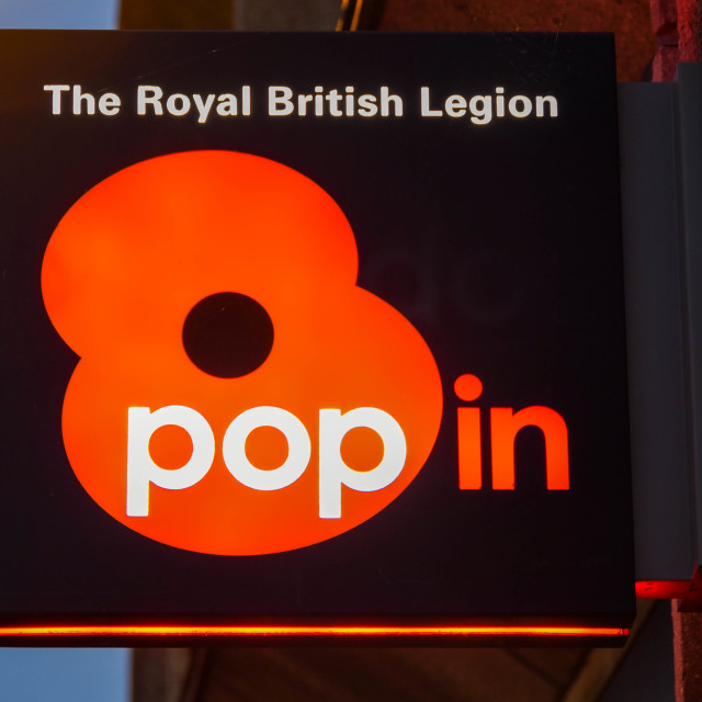 """""""Sign above a Royal British Legion """"pop in"""" poppy shop to promote Remembrance Day"""" stock image"""
