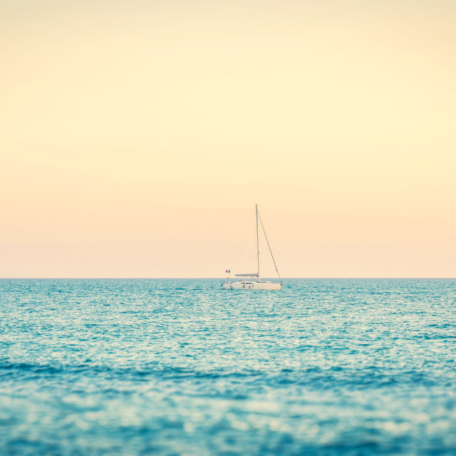"""Lonely boat on the sea near Tuscany coast few minutes before dusk"" stock image"