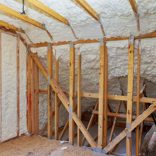 """New home construction with installation of attic with foam insulation"" stock image"