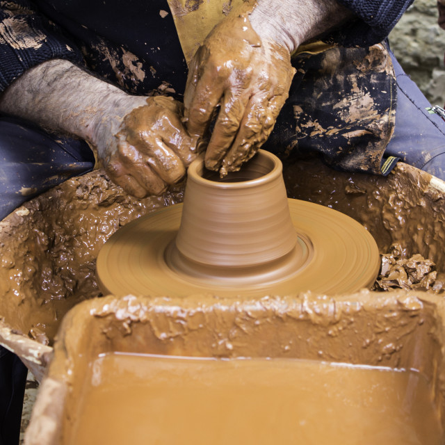 """Hands of man working and shaping clay, potter in pottery"" stock image"