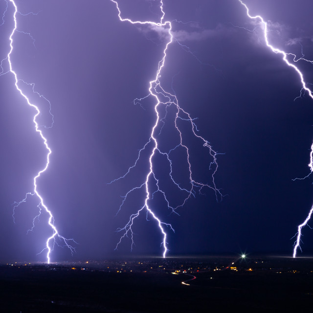 """Lightning bolts strike during a summer storm."" stock image"