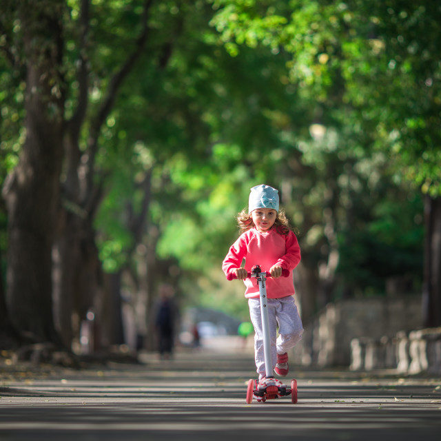 """""""The little girl rides the scooter in park"""" stock image"""