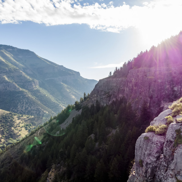 """""""A man sits on a ridge looking out to the mountains and valleys below with..."""" stock image"""