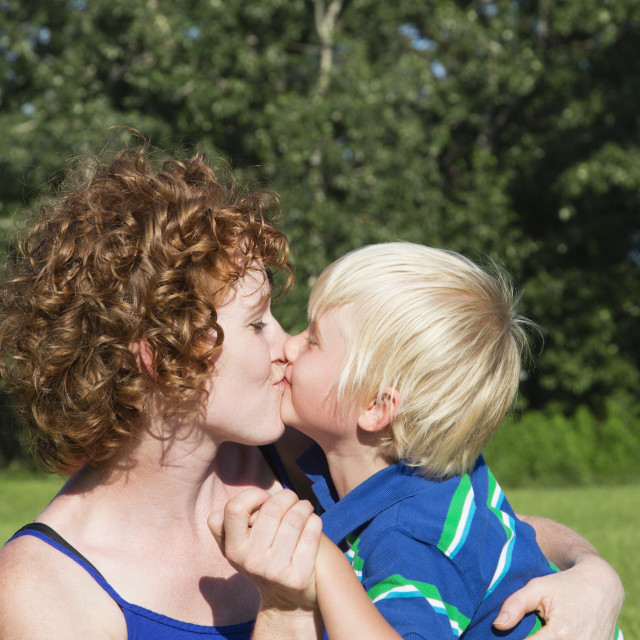 """""""A Mother Holds And Kisses Her Young Son; Stony Plain, Alberta, Canada"""" stock image"""