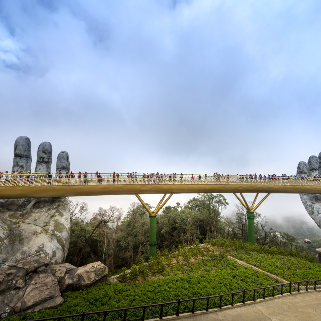 """""""The Golden Bridge is lifted by two giant hands in the tourist resort on Ba Na Hill in a foggy day at Danang, Vietnam"""" stock image"""