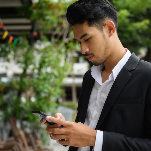 """Handsome Asian businessman with smartphone"" stock image"