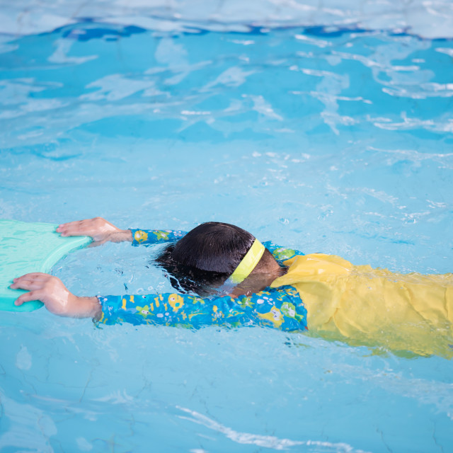 """Child practice swimming by floating foam"" stock image"