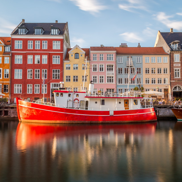 """Buildings along the Nyhavn in Copenhagen and a famous red boat"" stock image"