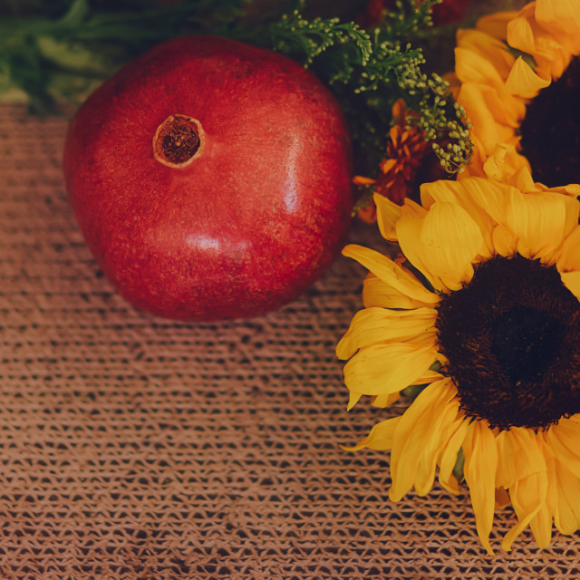 """""""Sunflowers and Pomegranate Arrangement on a Brown, Textured Background"""" stock image"""