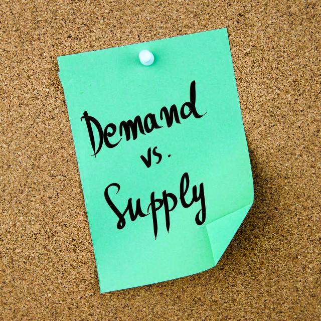 """Demand versus Supply written on green paper note"" stock image"