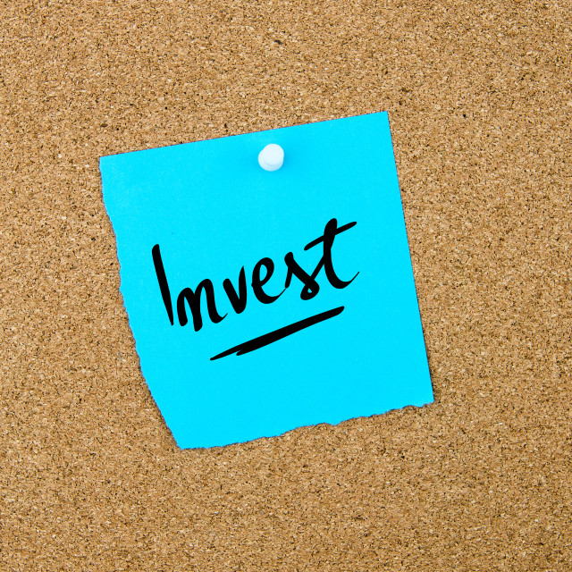 """""""Invest written on blue paper note"""" stock image"""