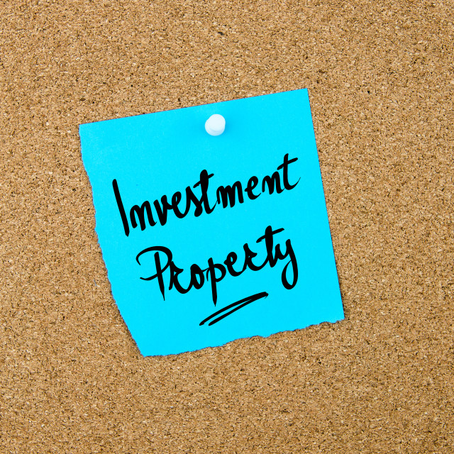 """""""Investment Property written on blue paper note"""" stock image"""