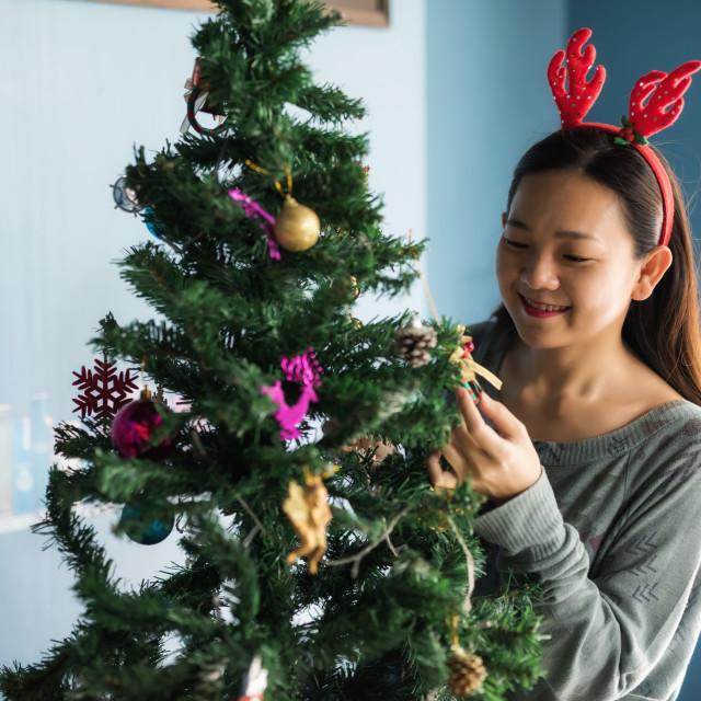 """Happy Asian woman at Christmas tree"" stock image"