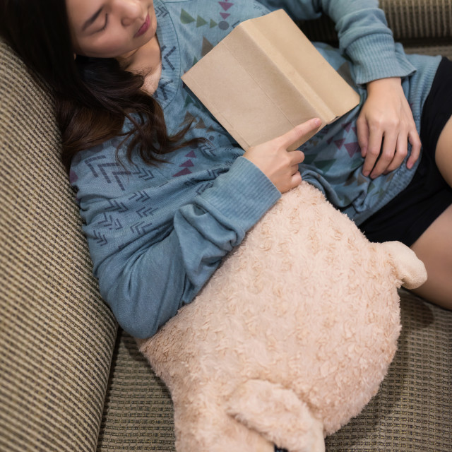 """woman hold book and sleep on sofa"" stock image"