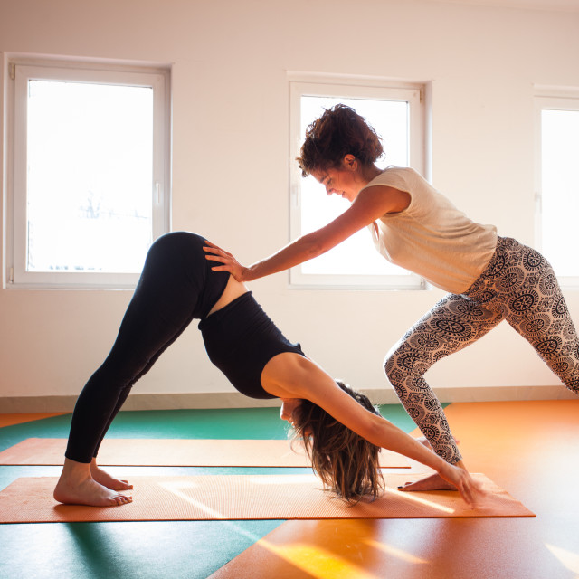 """yoga instructor assisting student in exercis"" stock image"