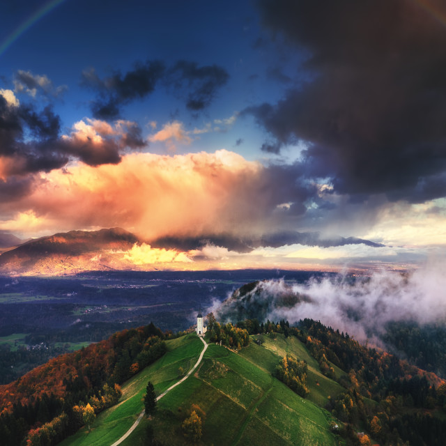 """""""Jamnik, Slovenia - Aerial view of rainbow over the church of St."""" stock image"""