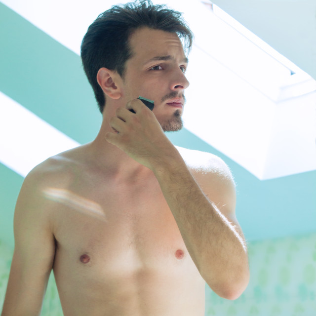 """""""young man trim beard in front of mirror"""" stock image"""