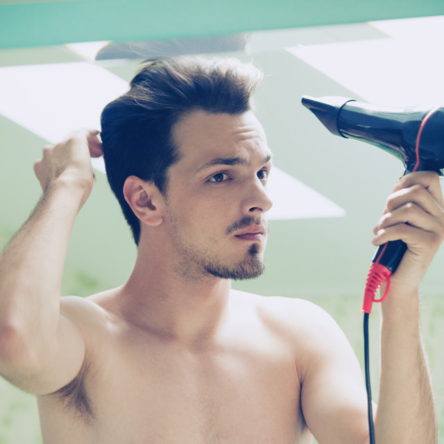 """""""young man dry hair with hair dryer in bathroom"""" stock image"""