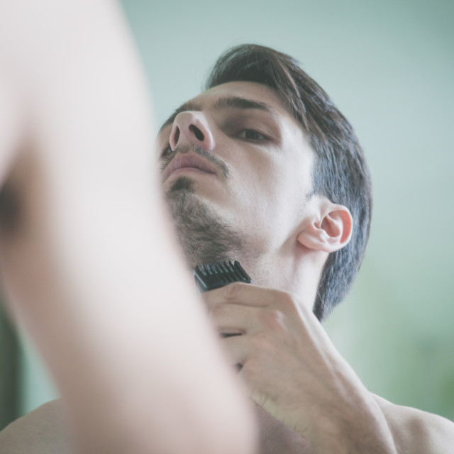 """""""closeup of young man trim beard in front of mirror"""" stock image"""