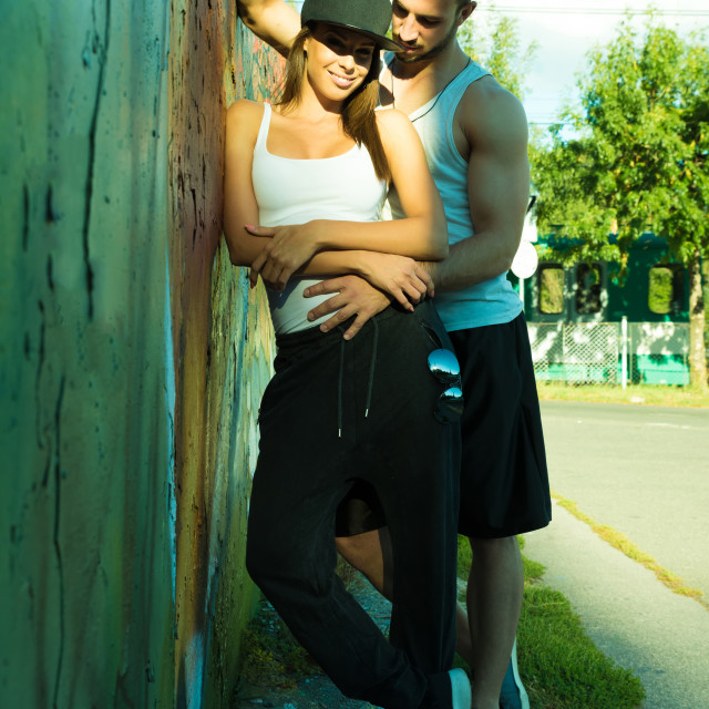 """Young Couple leaning against a wall in a urban environment"" stock image"