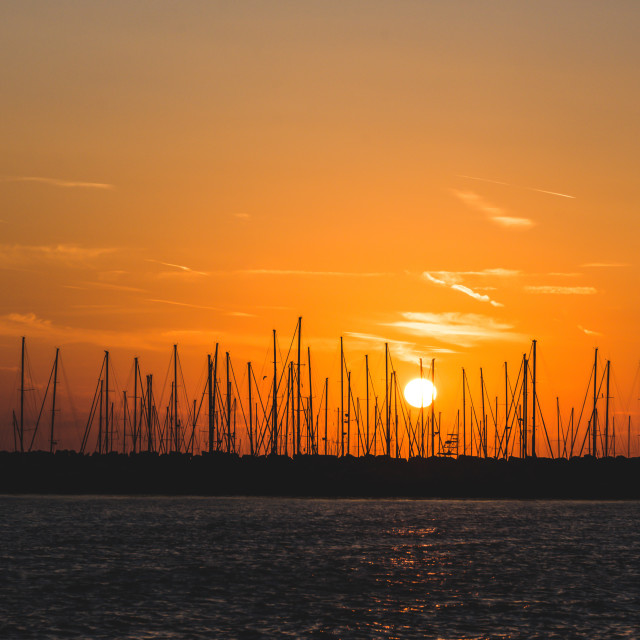 """""""Dusk behind several ships in a harbor"""" stock image"""