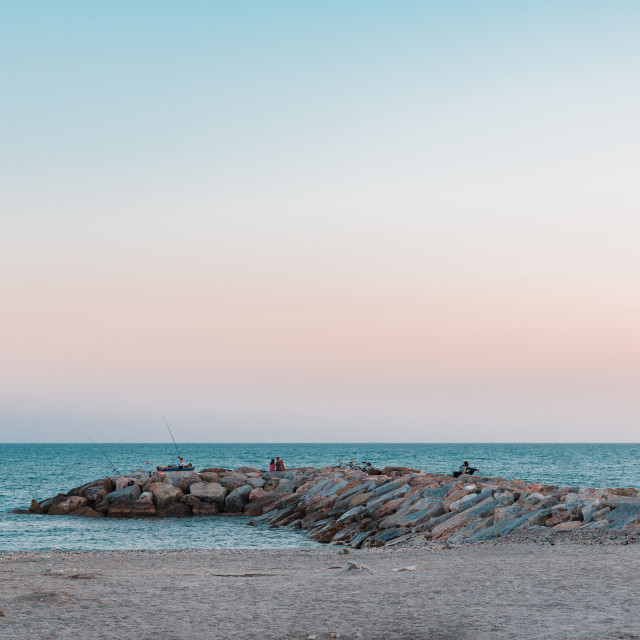 """""""Stone breakwater goes to sea with several persons"""" stock image"""