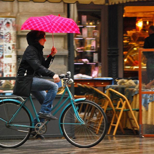 """Charming Italian Cyclist on a Rainy Day"" stock image"