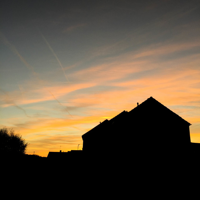 """""""Houses silhouetted against sunrise"""" stock image"""