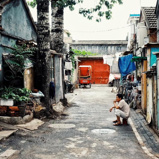 """Beijing / China - JUN 24 2011: man waiting outside of his home in a typical city hutong"" stock image"