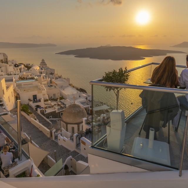 """Couple at restaurant overlooking Mediteranean Sea at sunset, Firostefani, Santorini"" stock image"