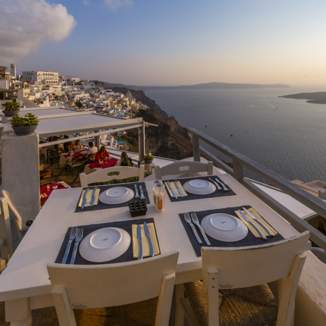 """""""View of restaurant and white washed houses at sunset, Fira, Firostefani, Santorini"""" stock image"""