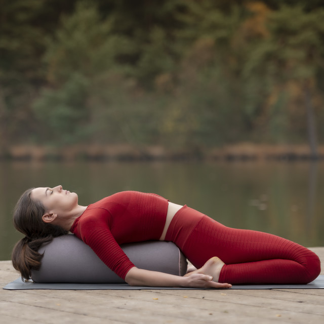 """""""woman practicing yoga on a jetty by a lake, using a yoga bolster to help position & pose."""" stock image"""