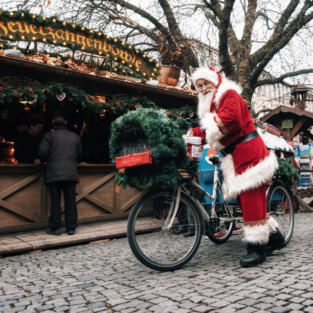 """""""Santa Claus drives a decorated bicycle with gifts in Munich."""" stock image"""