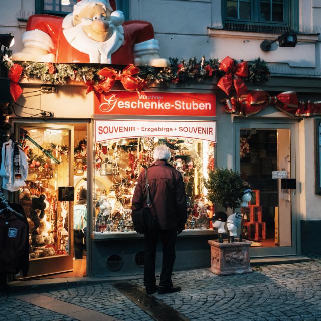 """Munich, Senior man looks at the shop window on Christmas eve"" stock image"