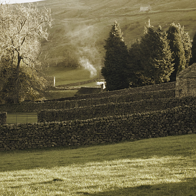 """Smoke rising in the sunlight in Muker, Swaledale"" stock image"