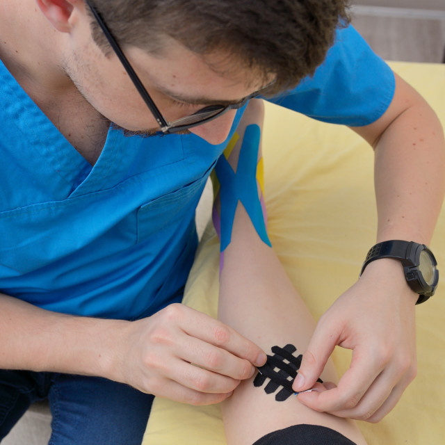 """""""Physiotherapist applying kinesiology tapes"""" stock image"""