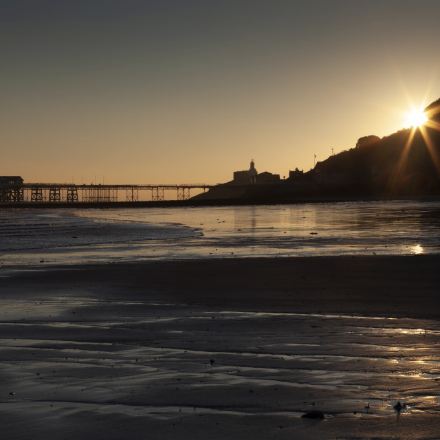 """Starburst sunrise at Mumbles Pier"" stock image"