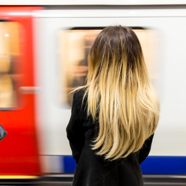"""Young woman with long blonde hair as London tube train arrives"" stock image"