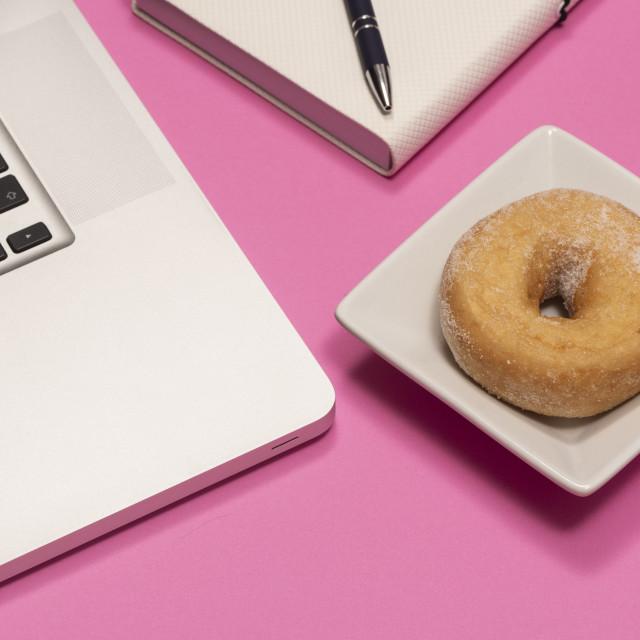 """pink desktop with doughnut snack alongside laptop and notebook."" stock image"