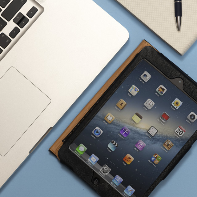 """""""laptop computer, iPad mini and a note book on a blue desk, flat lay."""" stock image"""