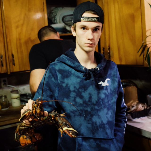 """""""local farmer young man with a typical lobster from the region preparing christmas dinner"""" stock image"""
