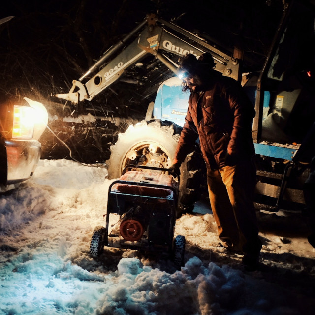 """""""local farmer man working outside with a generator during a strong snow hail storm"""" stock image"""