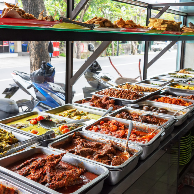 """Indonesian food buffet dishes consist of meat, chicken, seafood and vegetables at Javanese restaurant in Bali."" stock image"