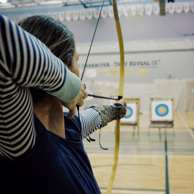 """""""young archer woman aiming with her bow and arrow to the aim inside a sport hall facility"""" stock image"""